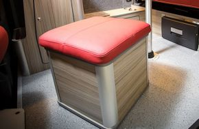 Cushioned storage seat for camper van